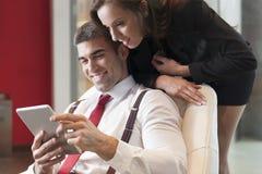 A mulher de negócios que olha sobre os colegas masculinos empurra apontar na tabuleta digital imagem de stock