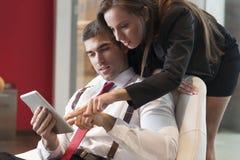 A mulher de negócios que olha sobre os colegas masculinos empurra apontar na tabuleta digital foto de stock
