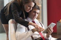A mulher de negócios que olha sobre os colegas masculinos empurra apontar na tabuleta digital fotografia de stock royalty free