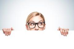 Mulher de negócios que olha sobre a parte superior do sinal branco Imagens de Stock