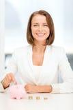 Mulher de negócios que põe euro- moedas no mealheiro Imagens de Stock Royalty Free