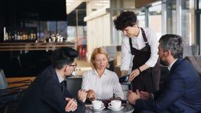 Mulher de negócios que paga pelo almoço com o smartphone durante o encontro de sócios video estoque