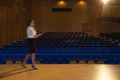 Mulher de negócios que pratica e que aprende o roteiro ao andar no auditório imagens de stock royalty free