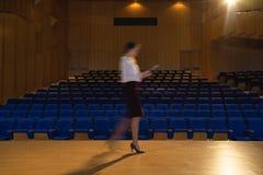 Mulher de negócios que pratica e que aprende o roteiro ao andar no auditório imagem de stock
