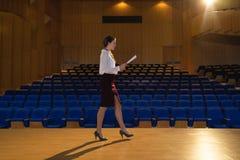 Mulher de negócios que pratica e que aprende o roteiro ao andar no auditório imagem de stock royalty free
