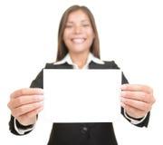 Mulher de negócios que prende o cartão em branco do sinal do negócio Imagens de Stock