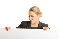 Mulher de negócios que prende o quadro de avisos vazio Fotografia de Stock Royalty Free