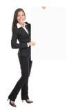 Mulher de negócios que prende o sinal vazio do quadro de avisos Imagens de Stock Royalty Free