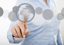 Mulher de negócios que pressiona o ícone do mundo no tela táctil digital Imagem de Stock Royalty Free