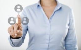Mulher de negócios que pressiona o ícone dos povos no tela táctil digital Fotografia de Stock