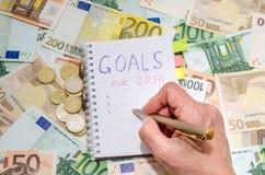mulher de negócios 2017 que redige a lista da definição dos anos novos contra a euro- cédula Foto de Stock