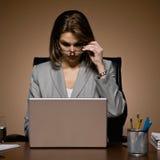 Mulher de negócios que remove os eyeglasses, trabalhando tarde fotografia de stock