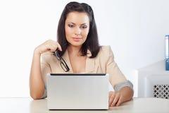 Mulher de negócios que senta e que olha o caderno Fotos de Stock Royalty Free