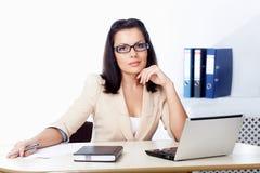 Mulher de negócios que senta-se atrás da mesa Imagens de Stock