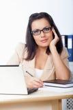 Mulher de negócios que senta-se atrás da mesa Fotografia de Stock Royalty Free