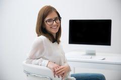 Mulher de negócios que senta-se em seu worplace no escritório Imagens de Stock Royalty Free