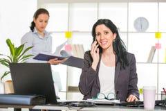 Mulher de negócios que senta-se em sua mesa com o colega no fundo Imagens de Stock Royalty Free