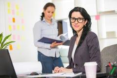 Mulher de negócios que senta-se em sua mesa com o colega no fundo Foto de Stock