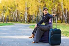 Mulher de negócios que senta-se em uma bagagem. Fotografia de Stock Royalty Free