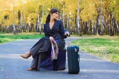 Mulher de negócios que senta-se em uma bagagem. Imagens de Stock Royalty Free