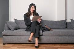 Mulher de negócios que senta-se lendo um tabuleta-PC Imagem de Stock Royalty Free