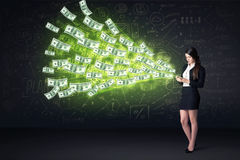 Mulher de negócios que senta-se na cadeira que guarda a tabuleta com notas de dólar Fotografia de Stock