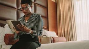 Mulher de negócios que senta-se na cama usando a tabuleta digital imagens de stock