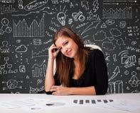 Mulher de negócios que senta-se na mesa com esquema e ícones do negócio Foto de Stock
