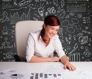 Mulher de negócios que senta-se na mesa com esquema e ícones do negócio Imagens de Stock Royalty Free