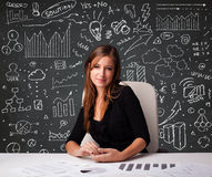 Mulher de negócios que senta-se na mesa com esquema e ícones do negócio Fotografia de Stock Royalty Free