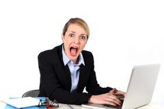 Mulher de negócios que senta-se na mesa de escritório que trabalha com o portátil no esforço que olha virado Foto de Stock Royalty Free