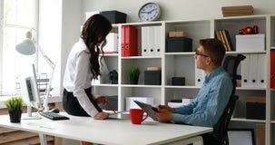 Mulher de negócios que senta-se na mesa e que discute o projeto com o gerente