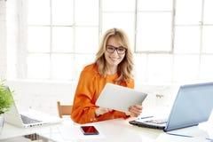 Mulher de negócios que senta-se na mesa de escritório e que usa sua tabuleta digitial foto de stock