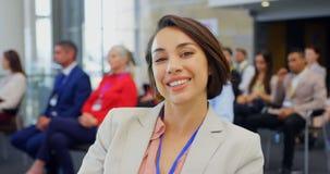 Mulher de negócios que senta-se no seminário do negócio e no 4k de sorriso vídeos de arquivo