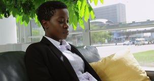 Mulher de negócios que senta-se no sofá e que usa o portátil no escritório 4k vídeos de arquivo