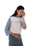 Mulher de negócios que sofre da dor de cabeça e da dor de estômago imagens de stock royalty free