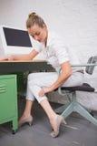 Mulher de negócios que sofre da dor de pé na mesa de escritório fotografia de stock