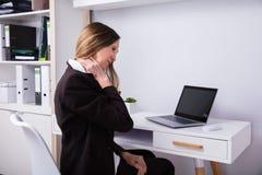 Mulher de negócios que sofre da dor de pescoço fotografia de stock