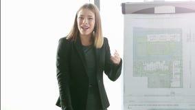 Mulher de negócios que sorri ao dar a apresentação aos colegas video estoque