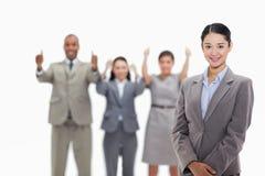 Mulher de negócios que sorri com os colegas de trabalho que aprovam no backgroun Fotos de Stock