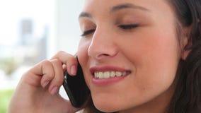 Mulher de negócios que sorri como fala em um telefone video estoque
