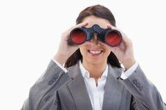 Mulher de negócios que sorri e que olha através dos binóculos Foto de Stock Royalty Free