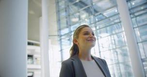 Mulher de negócios que sorri na entrada no escritório 4k video estoque