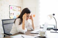 Mulher de negócios que tem a dor de cabeça no trabalho fotografia de stock
