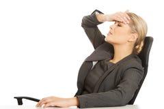 Mulher de negócios que tem a dor de cabeça enorme fotografia de stock