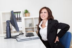 Mulher de negócios que tem a dor lombar no trabalho foto de stock