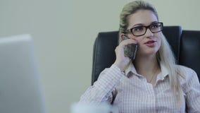 Mulher de negócios que tem um telefonema em um escritório filme