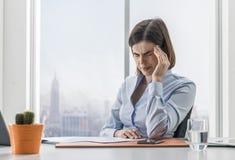 Mulher de negócios que tem uma dor de cabeça má no escritório fotografia de stock royalty free