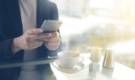Mulher de negócios que texting com seu móbil durante uma ruptura de café imagens de stock royalty free