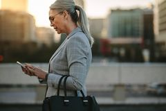 Mulher de negócios que texting no telefone ao andar exterior imagens de stock